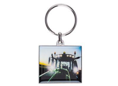Metalen sleutelhanger met een foto van een tractor